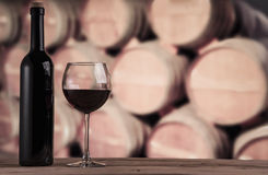 Red wine bottle with glass on the background of oak barrels. Wine background. Wine barrels in the wine cellar. Wine background Stock Photos