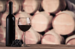 Red wine bottle with glass on the background of oak barrels. Wine background Stock Photo