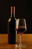 Red wine bottle with glass on black  background Royalty Free Stock Photography