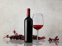 Red wine bottle glass bunch of grapes on marble background Stock Photo