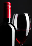 Red wine bottle and glass closeup on black Stock Photo