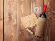 Red wine bottle, glass and corkscrew on wooden table Stock Photos