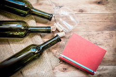 Red wine bottle, glass and grape shaped corks and red book Stock Photos