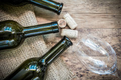 Red wine bottle, glass and grape shaped corks on wooden table Royalty Free Stock Images
