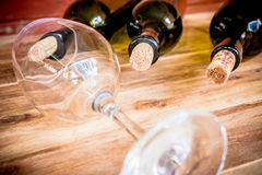 Red wine bottle, glass and grape shaped corks on wooden table Stock Images
