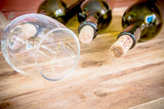 Red wine bottle, glass and grape shaped corks on wooden table Stock Photo