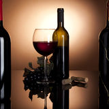 Red wine bottle, glass and grapes. Glass of red wine with opened bottle and black grapes, framed by two more wine bottles Stock Image