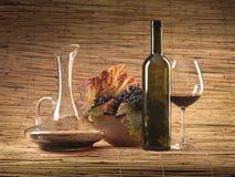 Red wine bottle, glass, grapes, decanter rustic. Bottle of red wine, glass, pitcher and grapes on wicker background Royalty Free Stock Photos