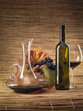 Red wine bottle, glass, grapes, decanter rustic. Bottle of red wine, glass, pitcher and grapes on wicker background Royalty Free Stock Images