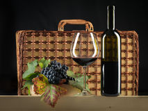 Red wine bottle, glass, grapes, picnic basket Royalty Free Stock Photos