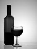 Red wine bottle and glass, monochrome black and white, backlit. Royalty Free Stock Photography