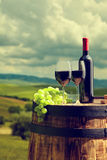 Red wine bottle and  glass on old barrel. Royalty Free Stock Image