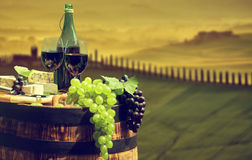 Red wine bottle and  glass on old barrel. Royalty Free Stock Images