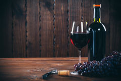 Red wine. Bottle and glass of red wine, grape and cork on wooden background Stock Image