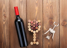 Red wine bottle, glass shaped corks and corkscrew Stock Image