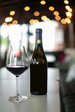 Red wine bottle and wine glass on table. Copyspace Stock Image