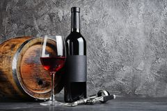 Red wine bottle with glass for tasting and wooden barrel in dark cellar. On gray concrete background stock photography