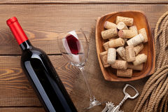 Red wine bottle, glass of wine, bowl with corks and corkscrew Stock Photo
