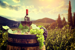 Red wine bottle and glass on wodden barrel Royalty Free Stock Images