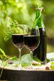 Red wine bottle and glass on wodden barrel Royalty Free Stock Photos