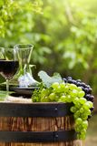 Red wine bottle and wine glass on wodden barrel. Beautiful Tuscany background.  stock image