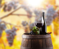 Red wine bottle and glass on wodden keg Stock Photography