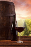 Red wine bottle and glass on wodden keg Royalty Free Stock Photos