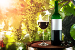 Red wine bottle and glass on a wooden barrel Stock Photo