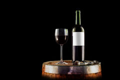 Red wine bottle and glass on a wooden barrel - isolated on black Stock Image