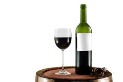 Red wine bottle and glass on a wooden barrel Royalty Free Stock Image