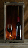 Red wine bottle and glass in wooden box Royalty Free Stock Image