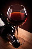 Red wine bottle and glass. On a wooden table stock photos