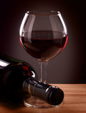 Red wine bottle and glass. On a wooden table royalty free stock photos