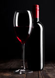 Red wine bottle and glass on wooden table black Royalty Free Stock Photos