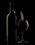 Red wine bottle and glasses. On dark background stock photos