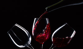Red wine. Bottle and glasses with red wine on a black background Royalty Free Stock Photo