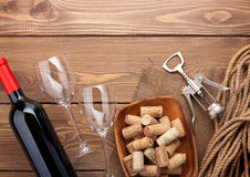 Red wine bottle, glasses, bowl with corks and corkscrew Royalty Free Stock Photos