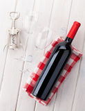 Red wine bottle, glasses and corkscrew Stock Images