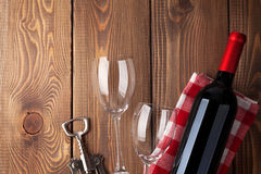Red wine bottle, glasses and corkscrew on wooden table Royalty Free Stock Images