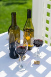Red wine and bottle. Glasses of red wine and bottle outdoors on a table Royalty Free Stock Photos