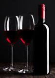 Red wine bottle and glasses on wooden table black. Background Royalty Free Stock Images
