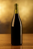 Red wine bottle on gold background. A red wine bottle isolated on gold background on a wooden table Stock Photos