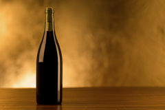 Red wine bottle on golden background. A red wine bottle isolated on a gold background and wooden table Royalty Free Stock Image