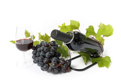 Red wine bottle and grape isolated. Red wine bottle , wine glass and grape vine branch isolated on white Royalty Free Stock Photography