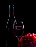 Red wine bottle, grapes and full glass Stock Images