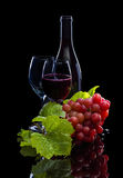 Red wine bottle, grapes and full glass Stock Photo