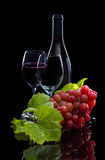 Red wine bottle, grapes and full glass Stock Photography