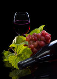 Red wine bottle, grapes and full glass Royalty Free Stock Image