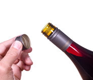 Red wine bottle opened screw top. Red or rose wine in screw top wine bottle  isolated against white with hand holding the cap by the neck of bottle Royalty Free Stock Photos