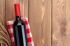 Red wine bottle over towel on wooden table Stock Photography